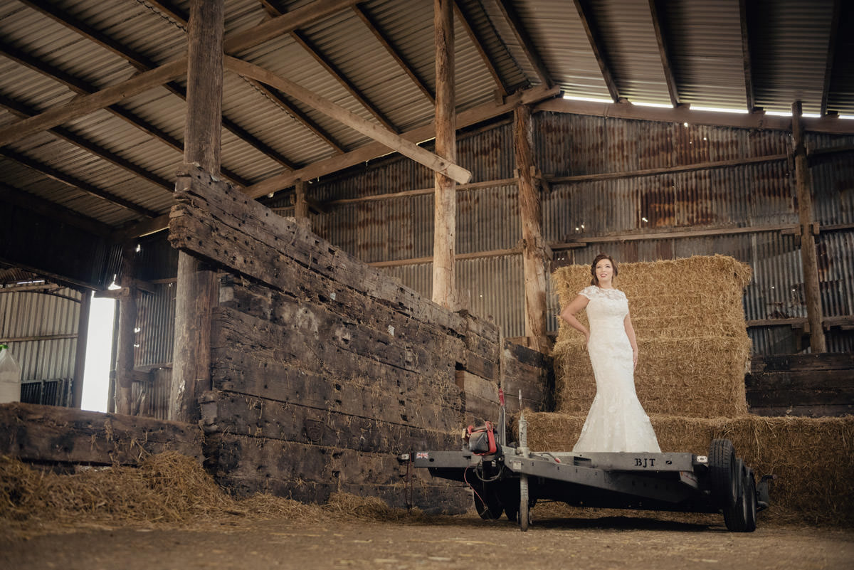 Bride standing on a trailer in a hay barn