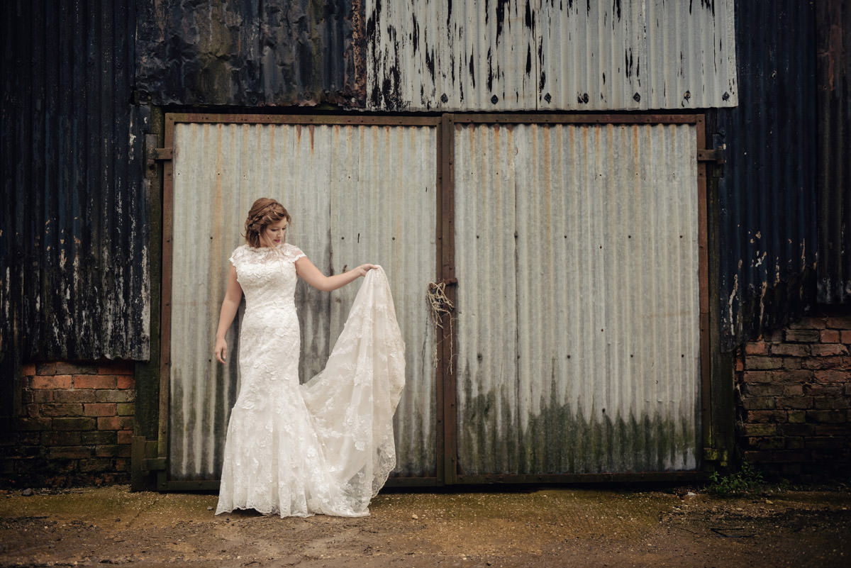 Photo of a bride in front of old corrugated doors on a farm in Northampton