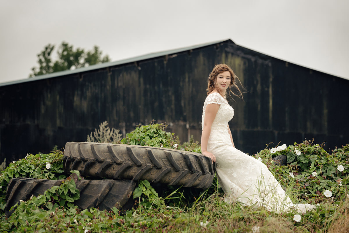 Bride sitting on a pile of old tyres on a farm in Northampton