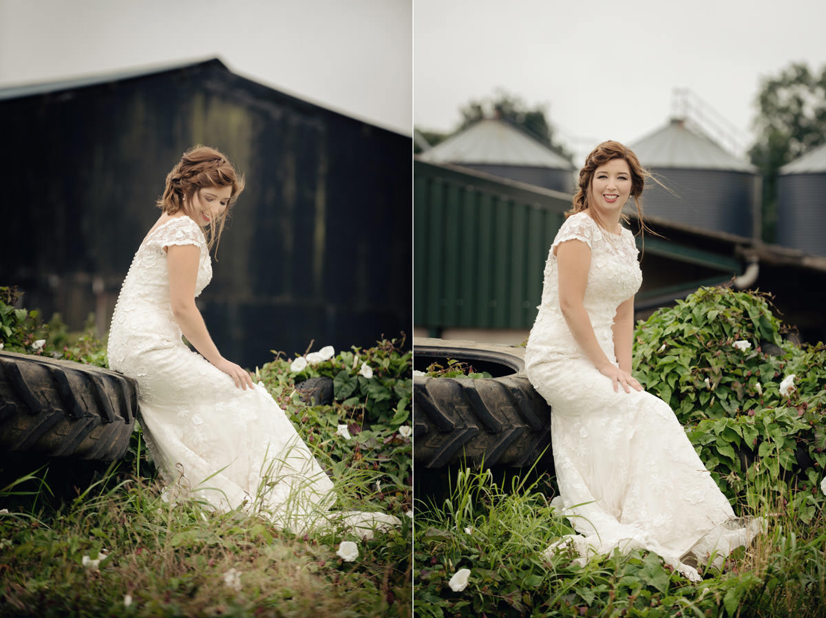 Bride sitting on a pile of old tyres on a farm in Northamptonshire