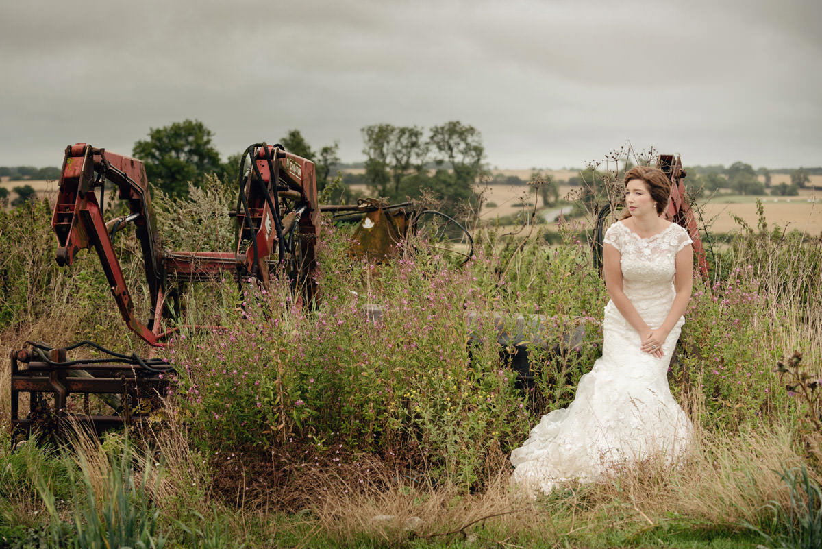 Bride sitting on machinery on a farm in Northampton