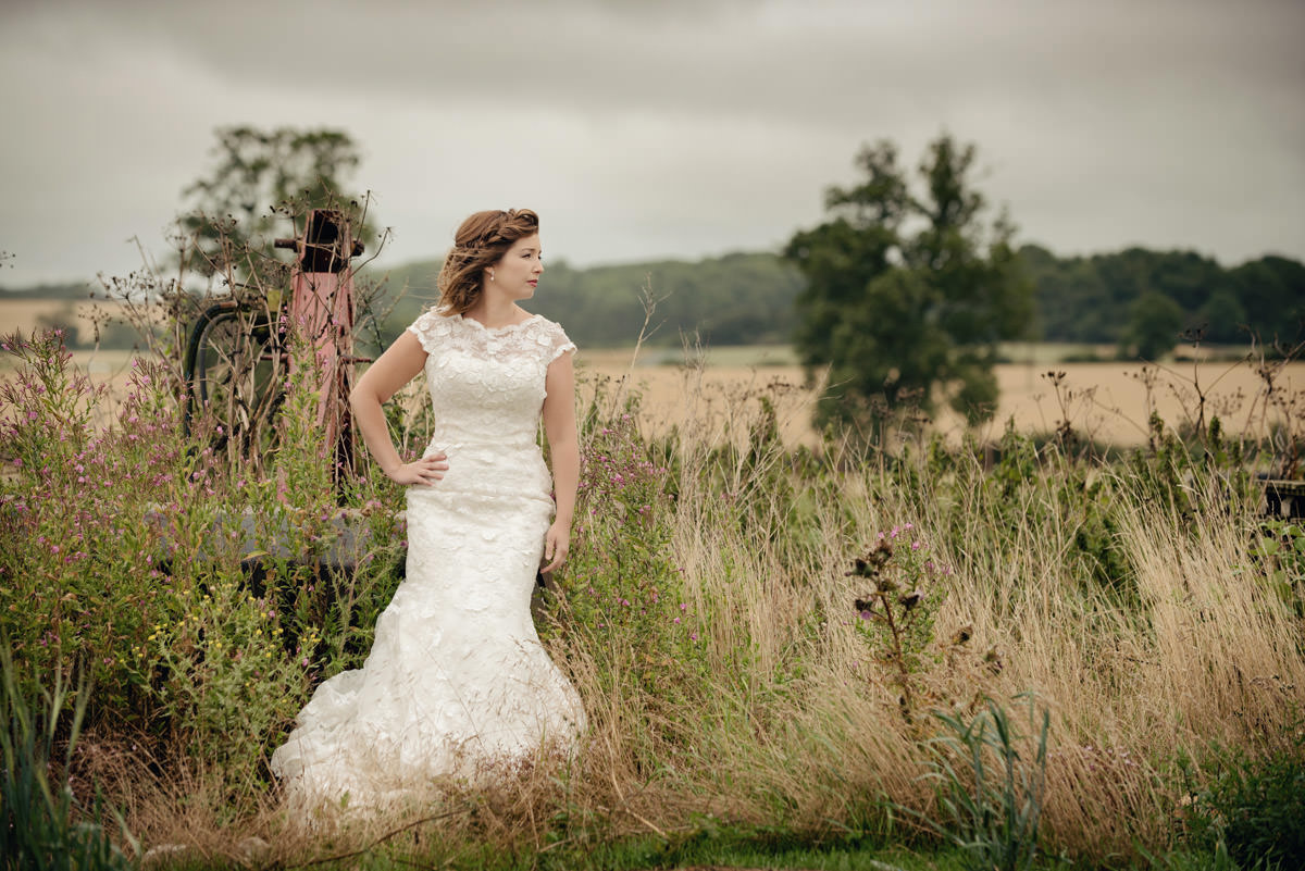 Bride leaning on a trailer amongst long grasses on a farm in Northampton