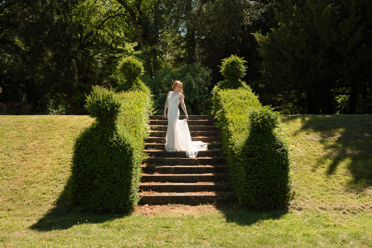 A bride on the steps in the gardens at Pipewell Hall