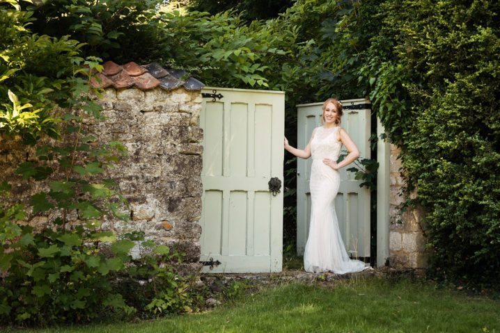 Bride in front of a rustic door at Pipewell Hall