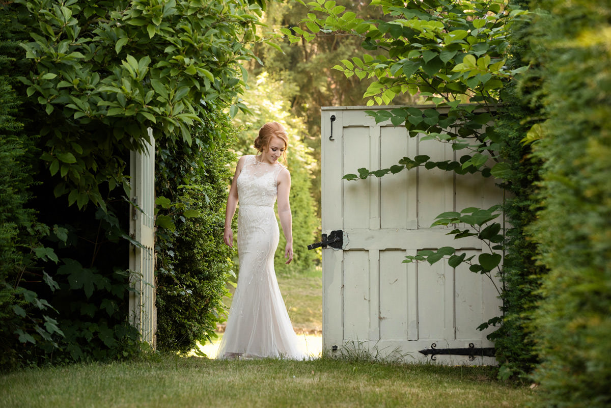 Bride posing for a photo by some old rustic doors at Pipewell Hall