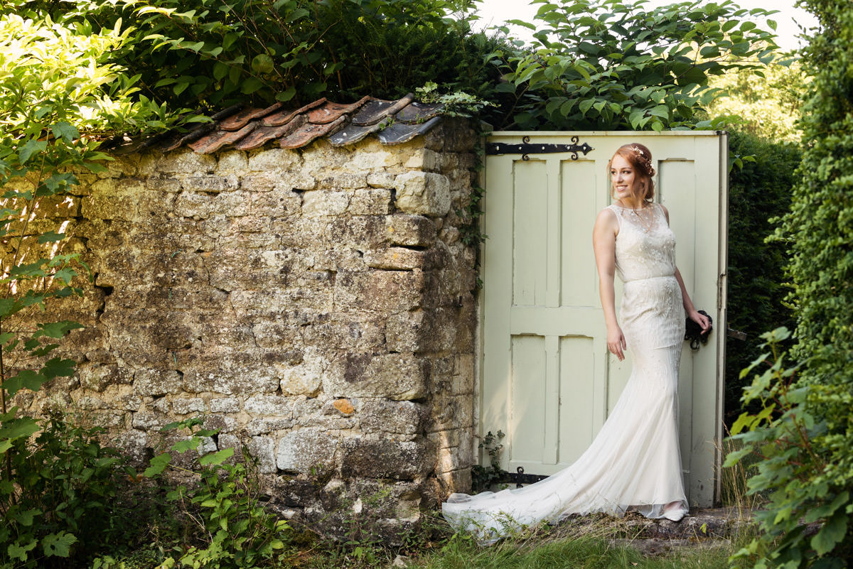 Portrait of a bride by an old stone wall at Pipewell Hall