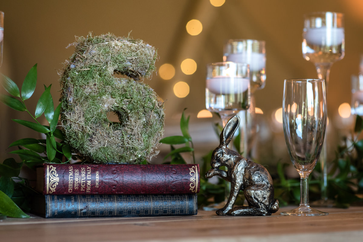 A moss covered table number for a tipi wedding at Pipewell Hall