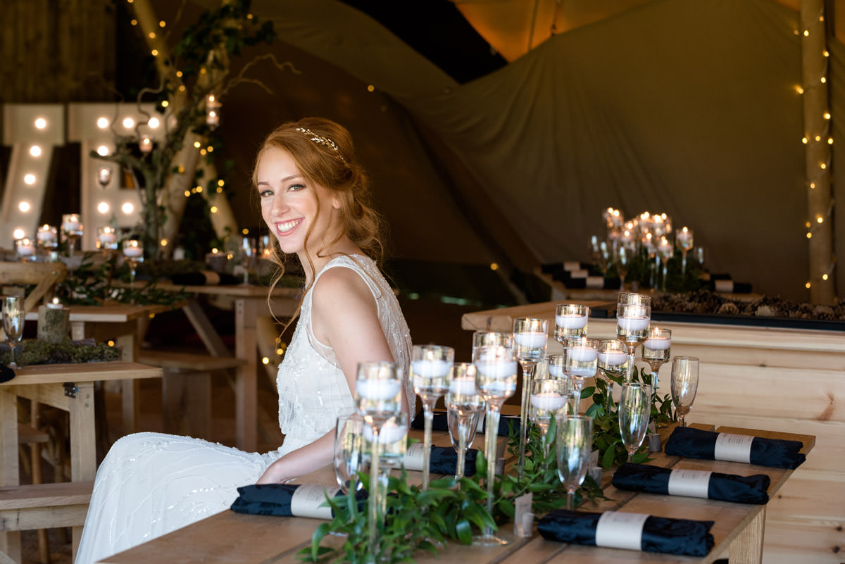 A bride sitting at the dinner table at a tipi wedding at Pipewell Hall