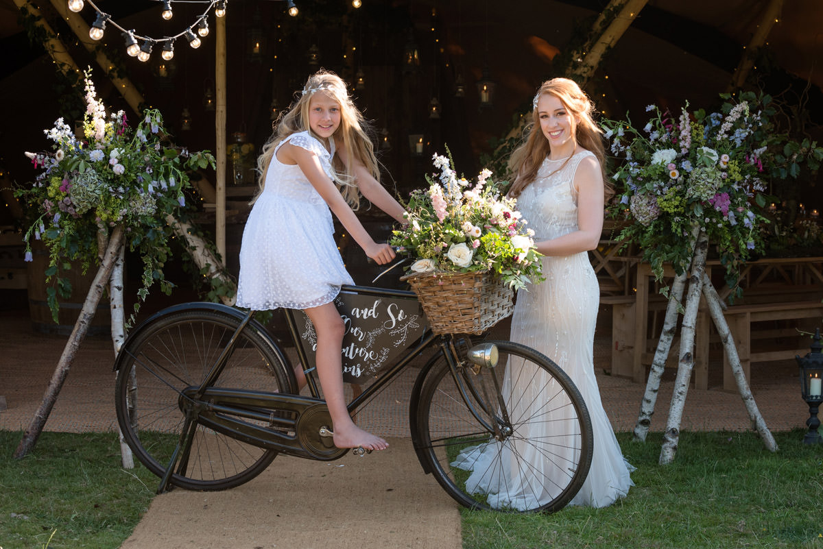 A vintage bike with a basket of flowers at a tipi wedding at Pipewell Hall