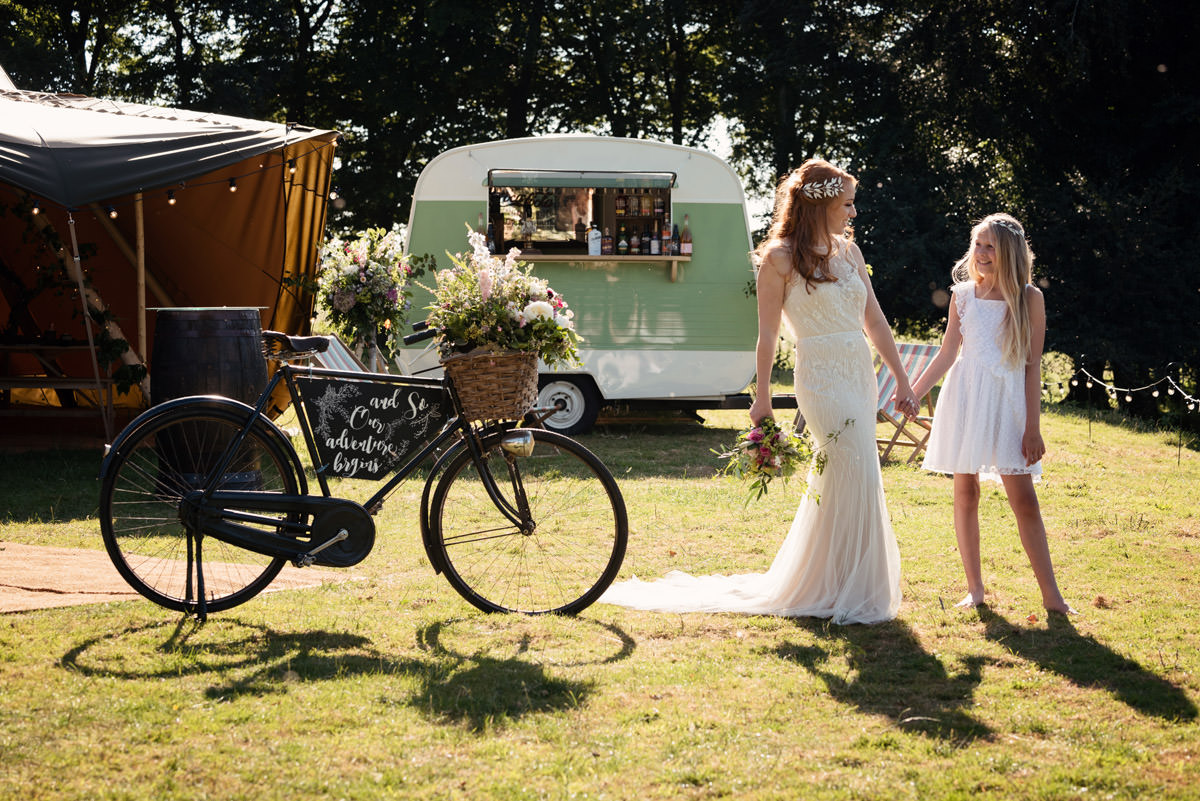 A bride & flower girl with a vintage bike at a tipi wedding at Pipewell Hall