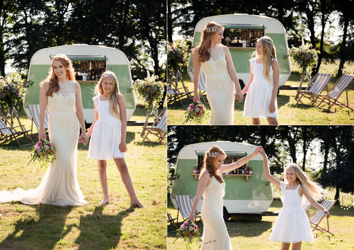A bride & flower girl having photos in front of a vintage caravan at a tipi wedding at Pipewell Hall