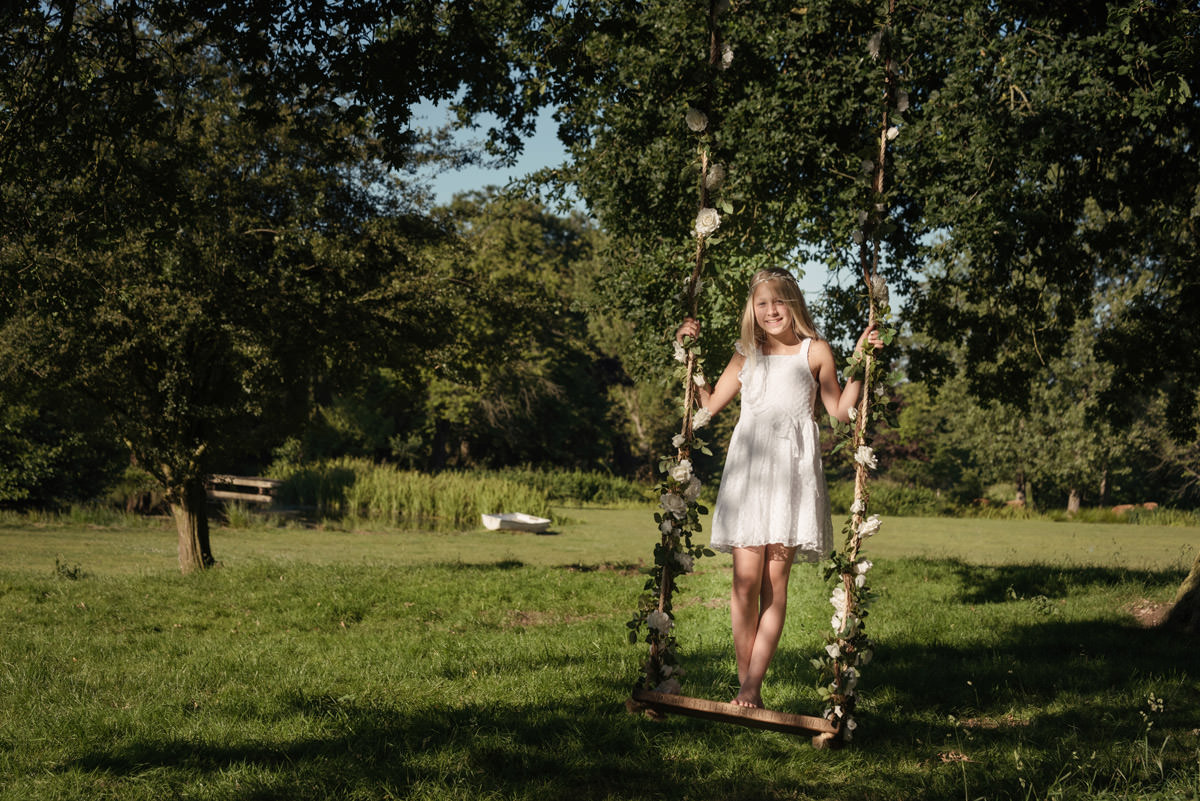 A flower girl playing on a swing at a tipi wedding at Pipewell Hall