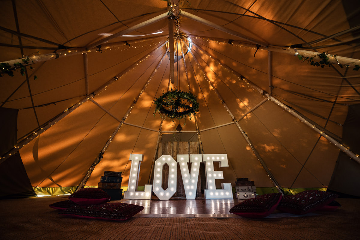 A dancefloor with a LOVE sign for a tipi wedding at Pipewell Hall