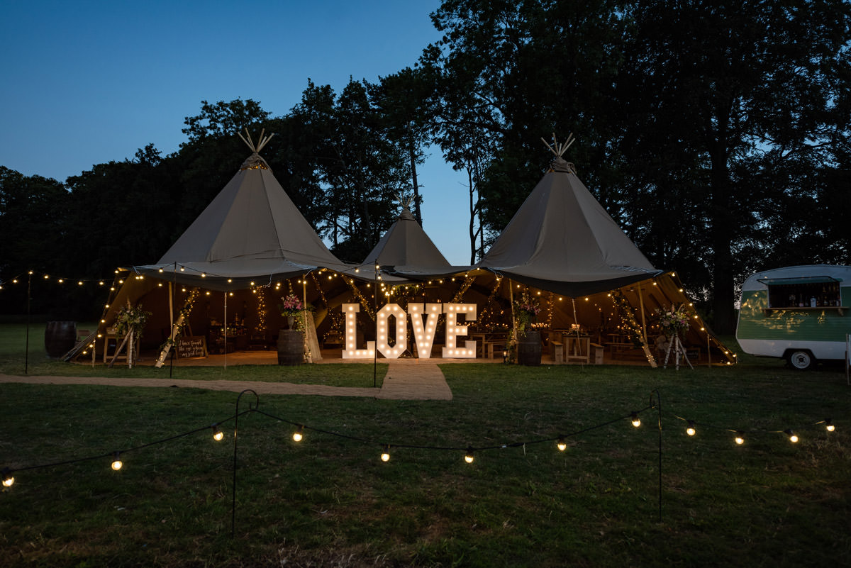 A tipi lit up at night at a wedding at Pipewell Hall in Northants