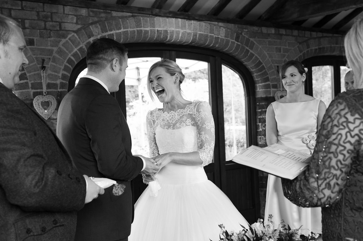 Bride laughing during wedding ceremony at Dodmoor House