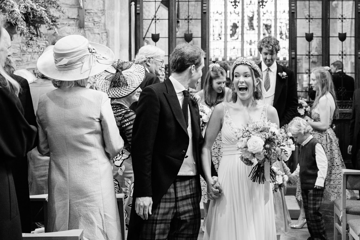 Bride laughing walking down the aisle at Geddington Church, Northampton