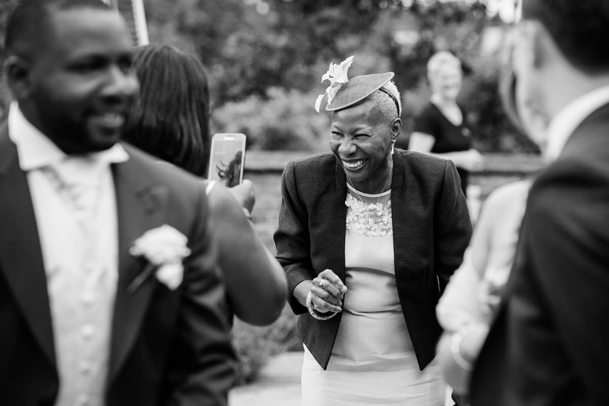 Mother of the Groom laughing as she arrives at Dodmoor House in Northampton
