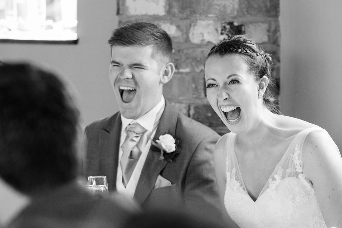 Bride & Groom laughing during the speeches at Dodmoor House in Northampton