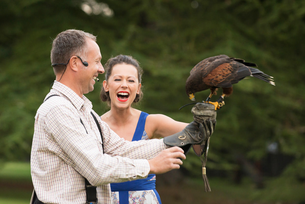 Wedding guest laughing during falconry display at Holdenby House in Northampton