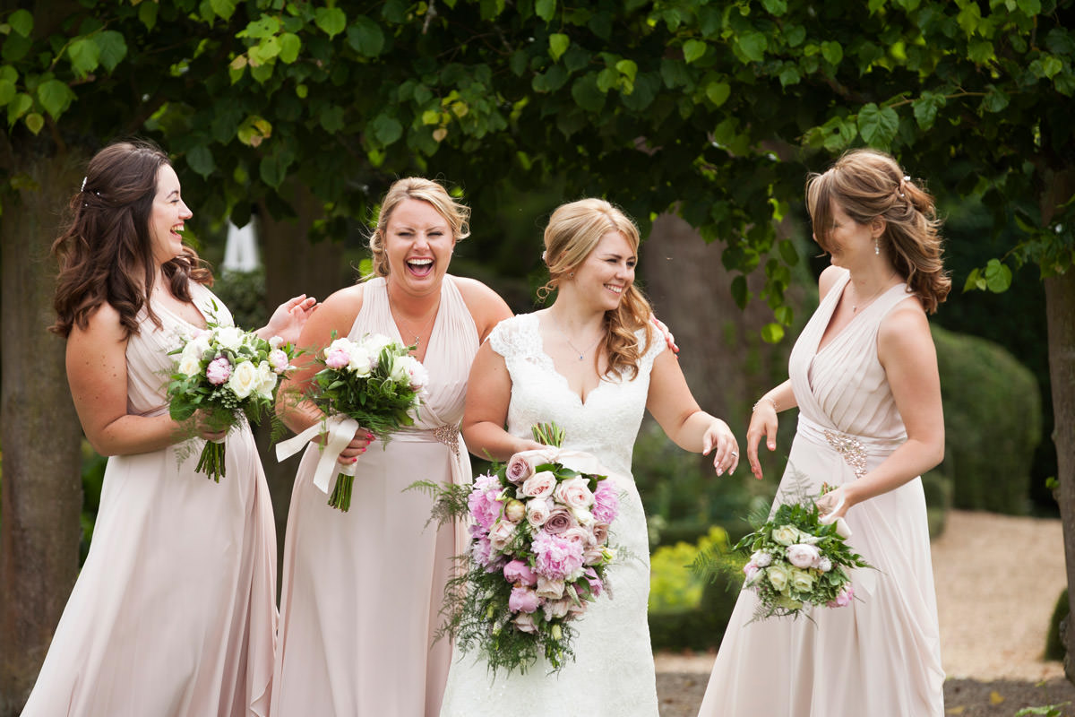 Bride & her bridesmaids laughing during the group photos at Kelmarsh Hall in Northampton