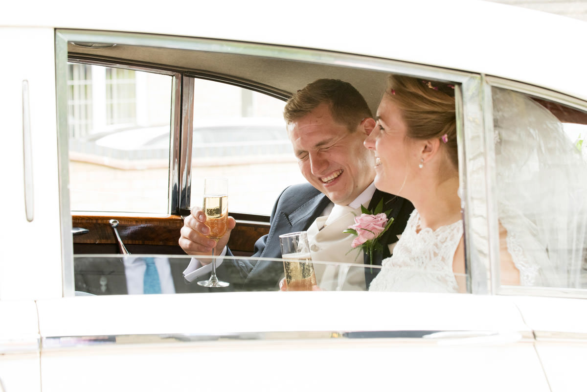 Bride & Groom laughing in the wedding car as they leave church in Wollaston, Northants