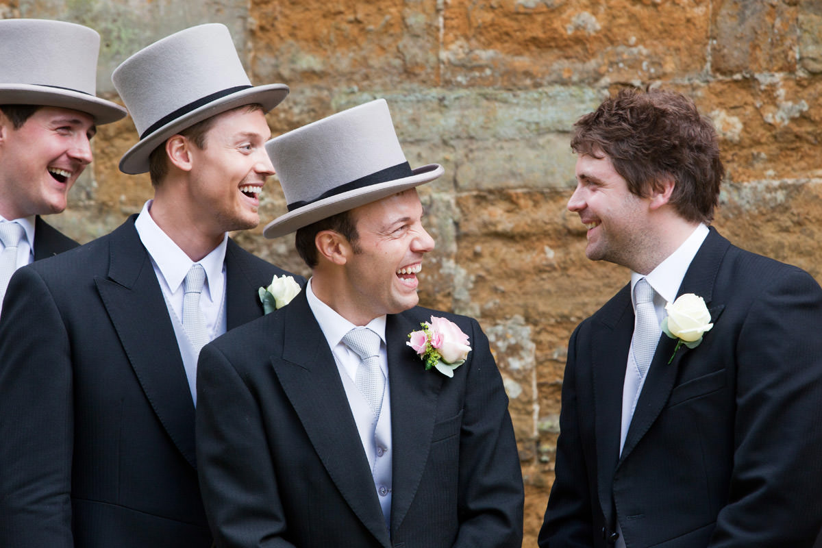Groom laughing with his Groomsmen at church in East Haddon, Northampton