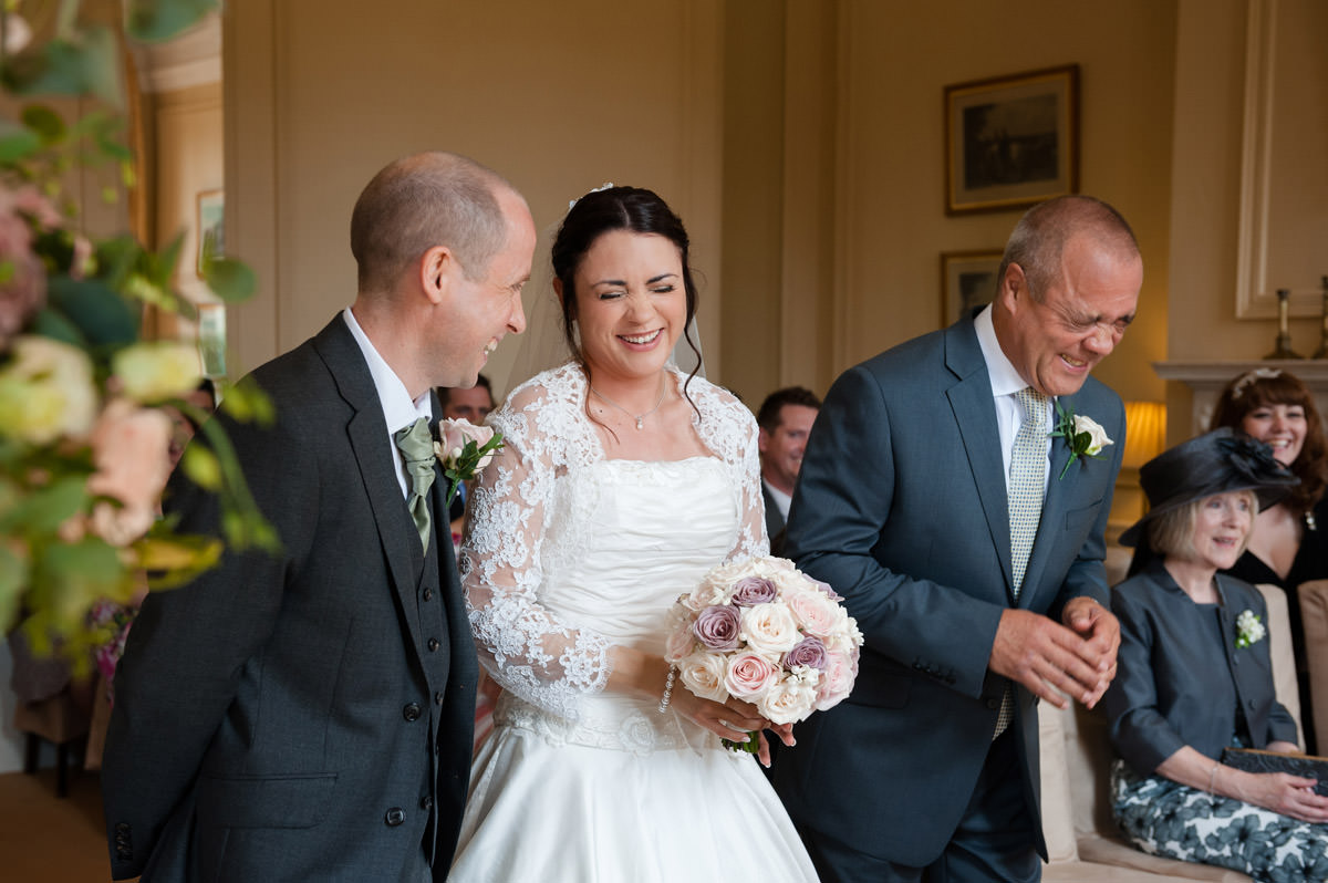 Father of the Bride laughing as he gives the Bride away at Rushton Hall in Northants