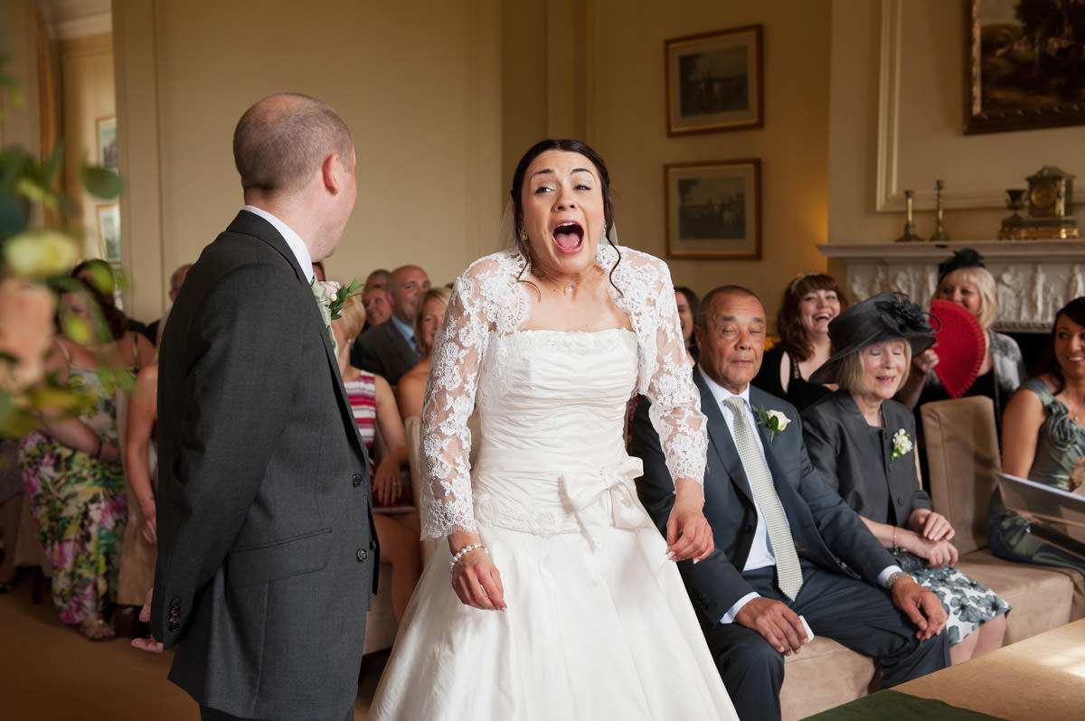 Bride laughing as she gets her vows wrong at Rushton Hall in Northants