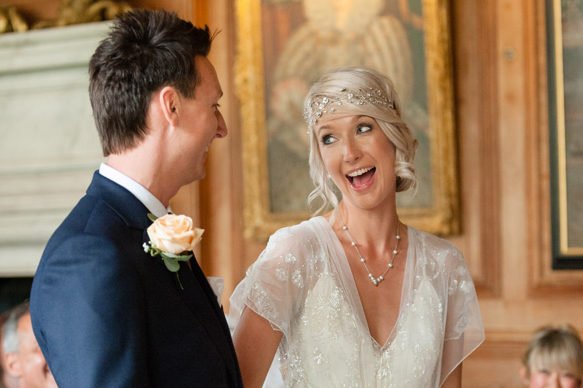 Bride & Groom laughing as they make their wedding vows at Boughton House in Northamptonshire