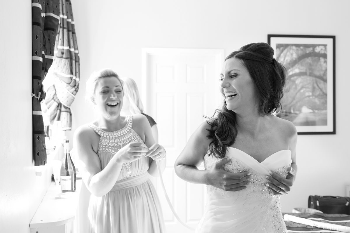 Bride laughing as she's laced into her wedding dress at Dunchurch Park in Rugby