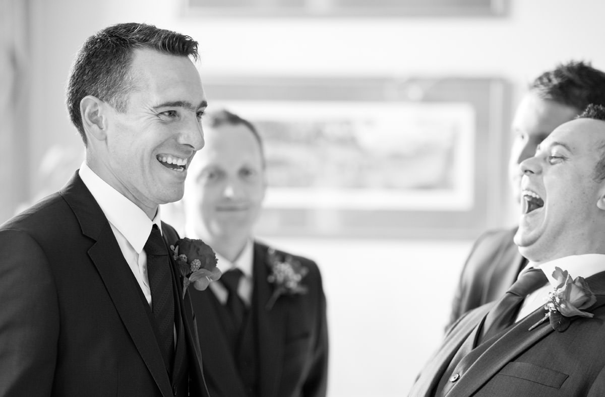 Groom laughing with his Groomsmen before the wedding at Rushton Hall in Northants