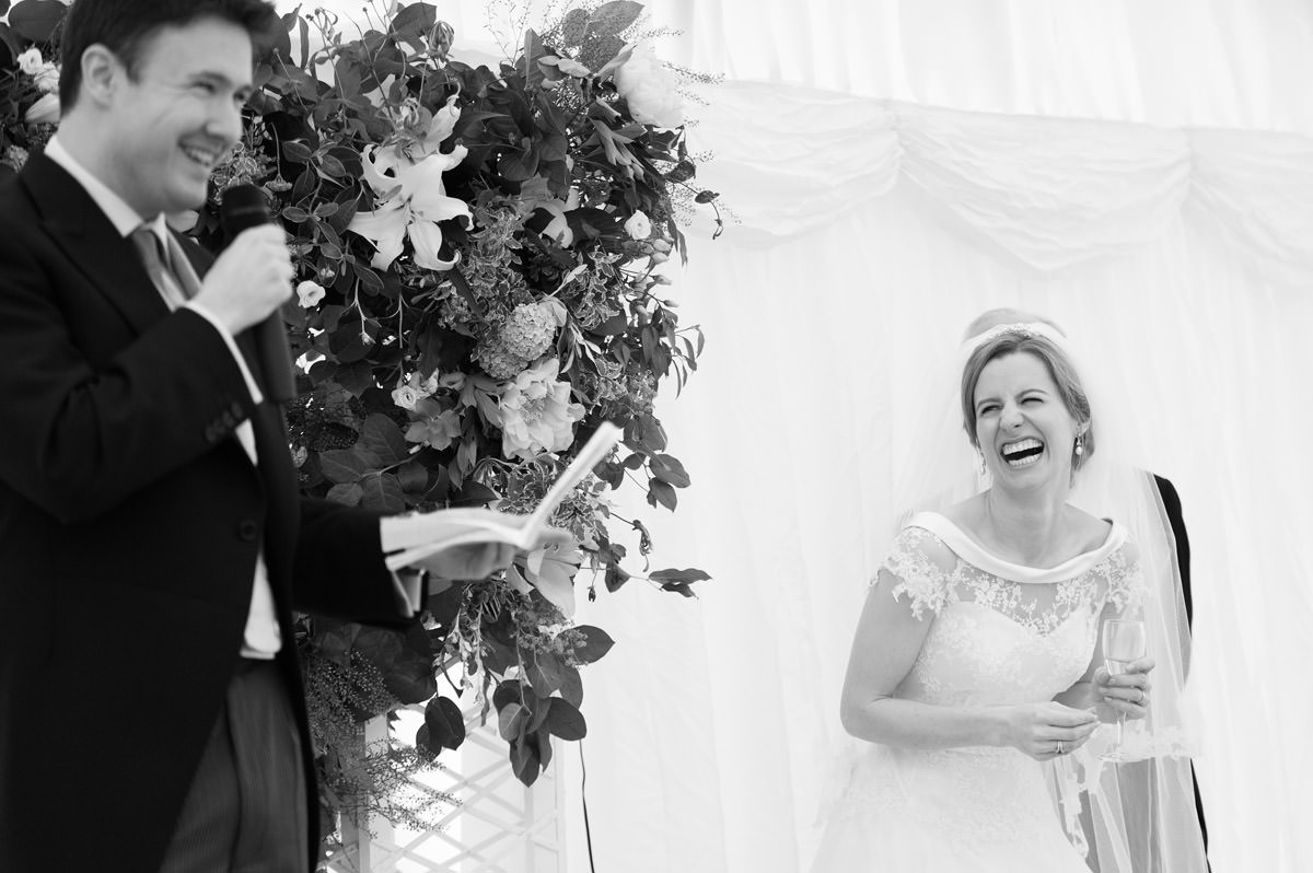 Bride laughing at the Groom's speech at a marquee wedding in Northampton