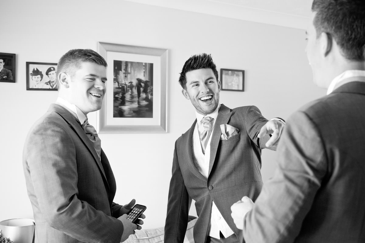 Best Man laughing with the Groom as they get ready for the wedding in Stony Stratford