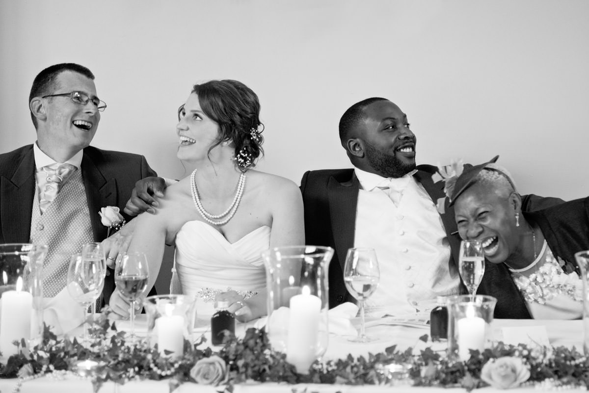Bride & Groom laughing with their parents during the speeches at Dodmoor House in Northants