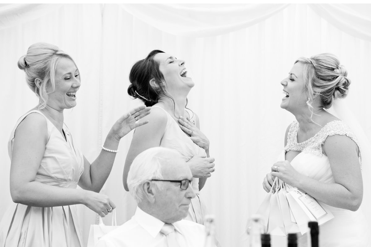Bride laughing with her bridesmaids during the speeches at Dunchurch Park in Rugby