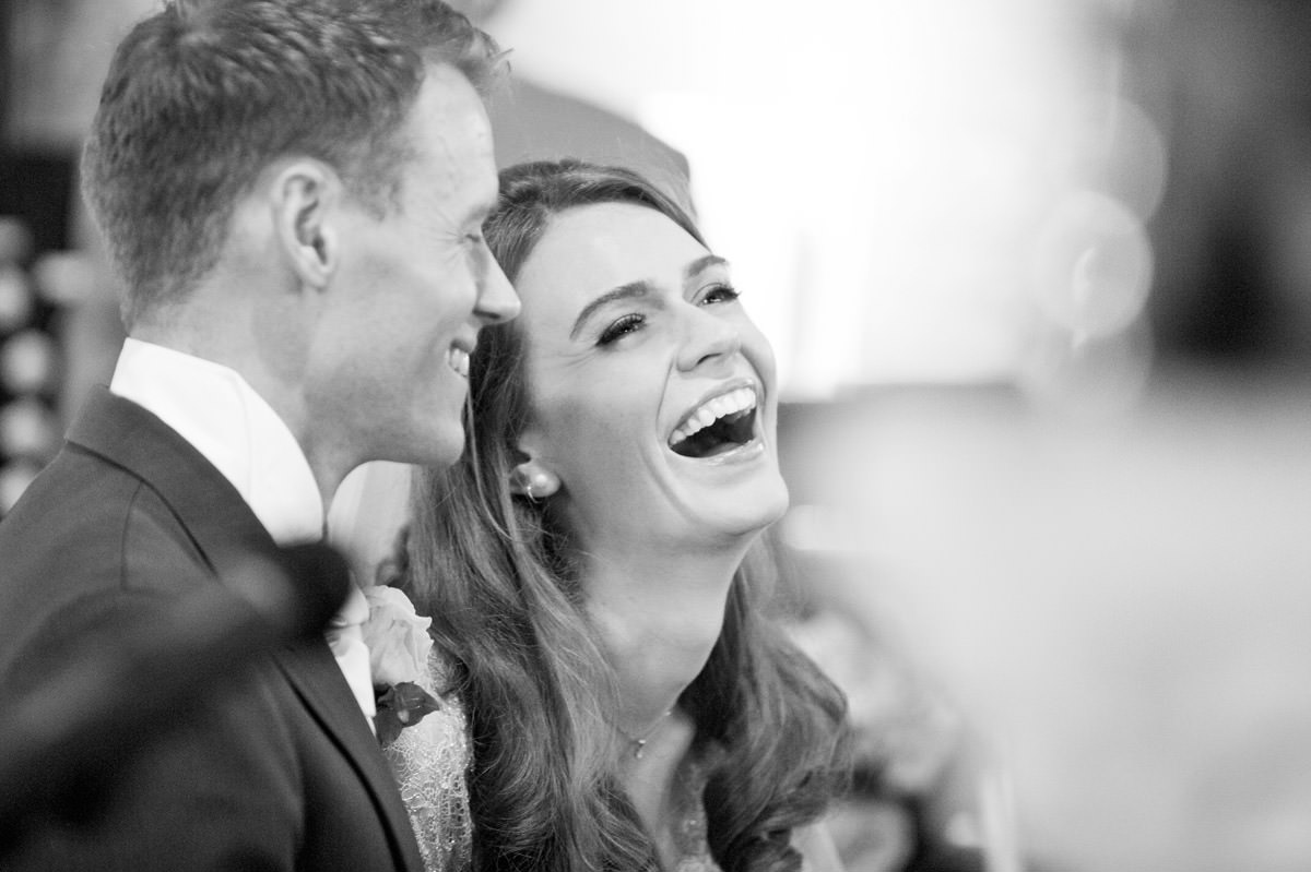 Bride laughing during the wedding ceremony at Woodnewton church