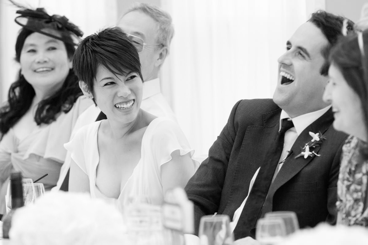Bride and Groom laughing during the wedding speeches at Pembroke Lodge in Richmond Park