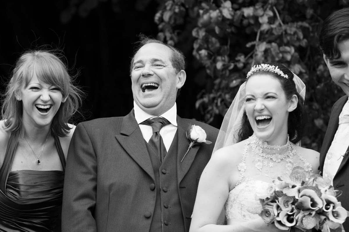 Bride laughing with her family during the group photos at Notley Abbey in Thame