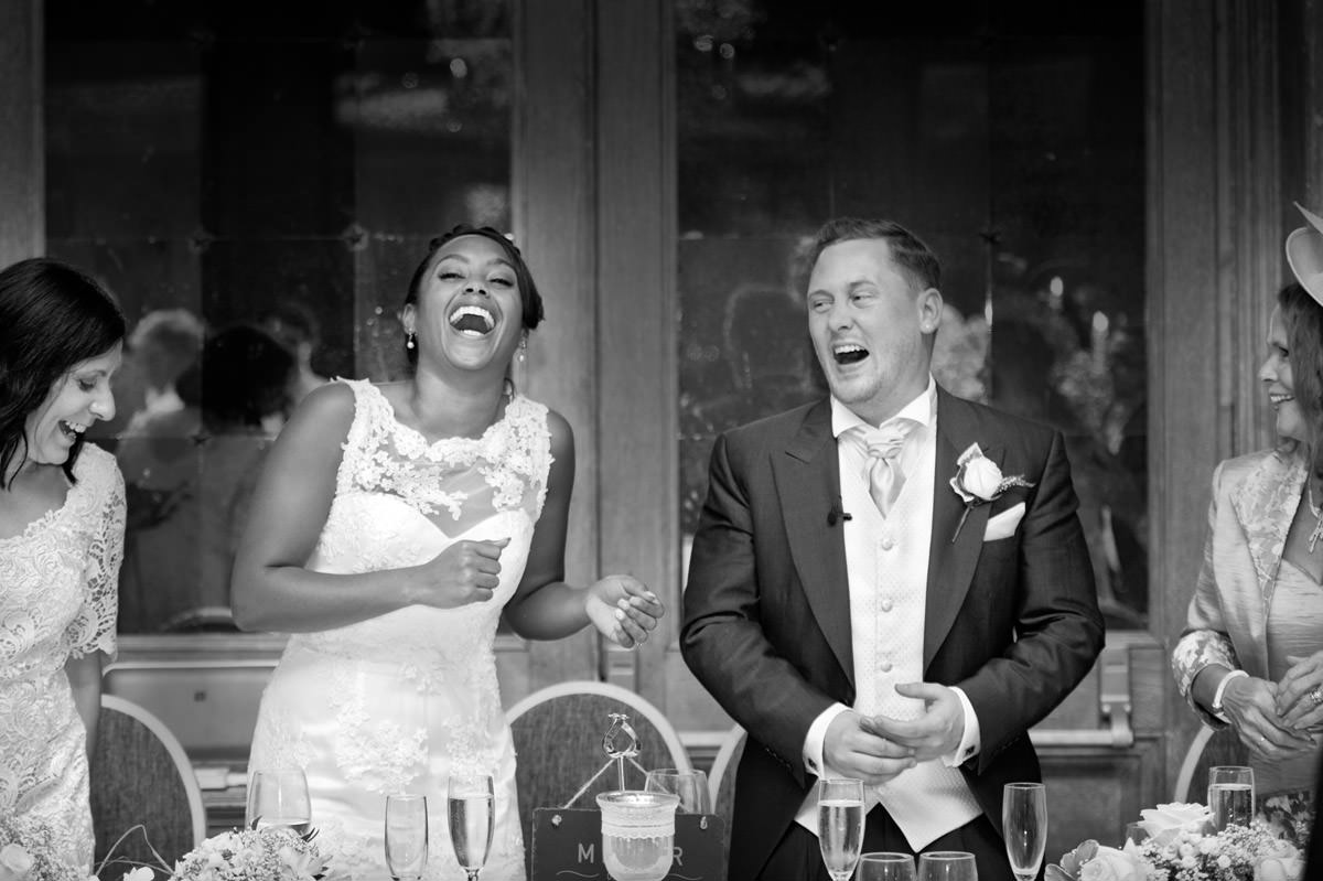 Bride & Groom laughing during the Father of the Bride's speech at Fawsley Hall in Northants