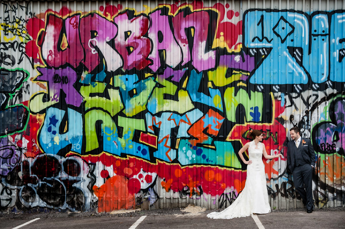 Bride & groom by grafitti wall in Shoreditch