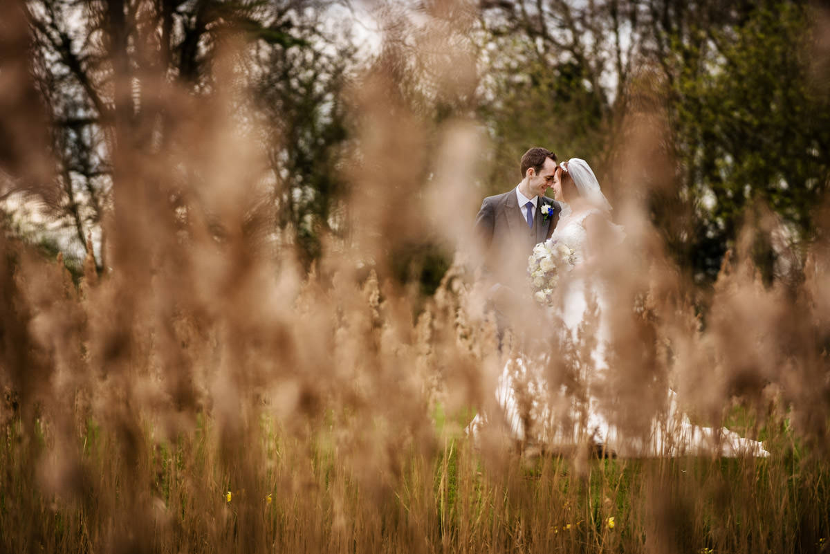 Bride & groom shot through long grass at Chicheley Hall