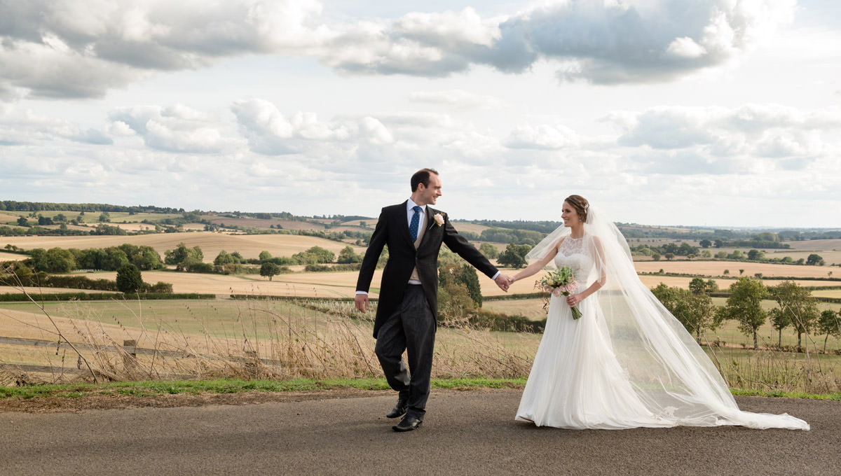 Bride & Groom walking with a view of Northamptonshire countryside in the background