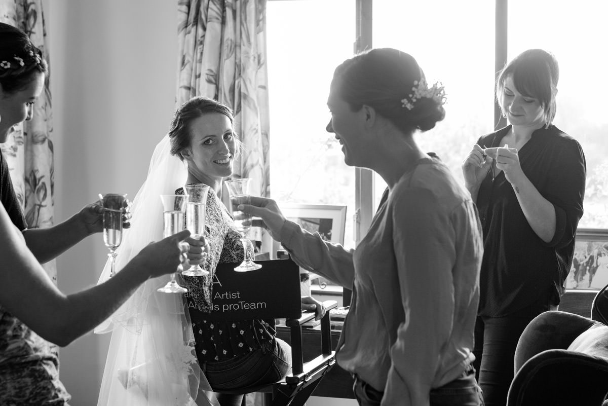 Bride & bridesmaids toasting with champagne while getting ready