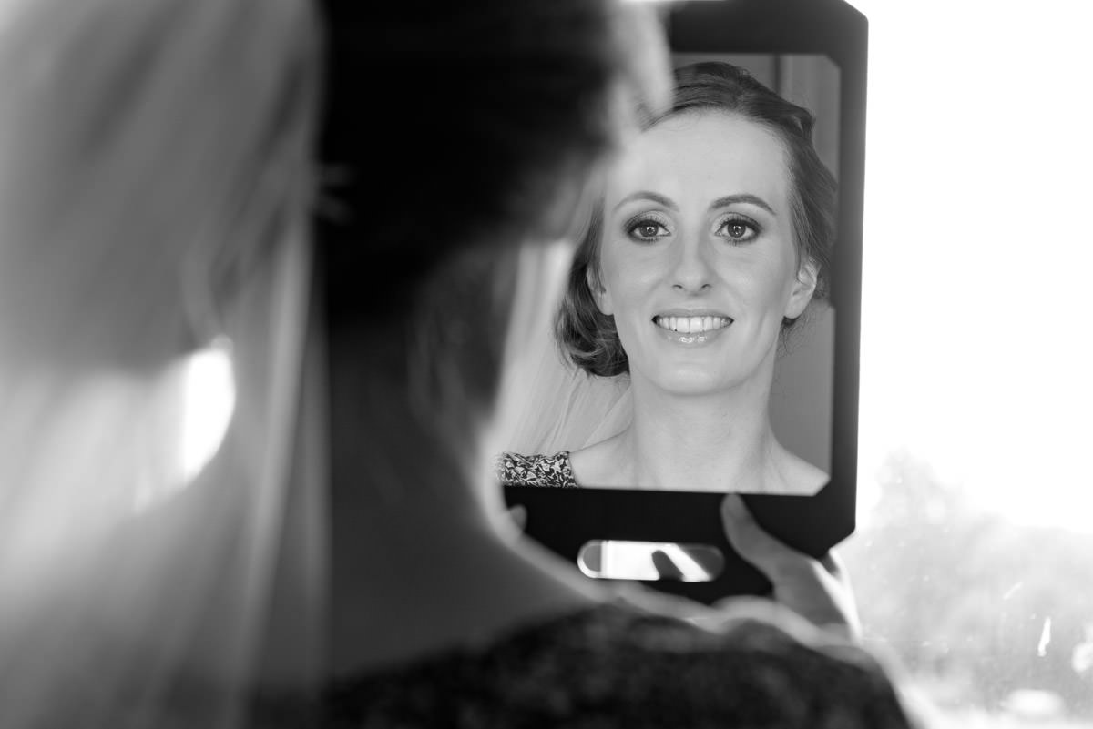 Bride checking her make-up in the mirror