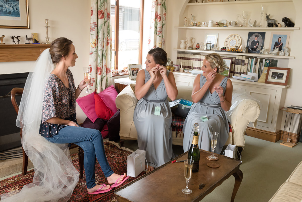 Bridesmaids putting on their earrings