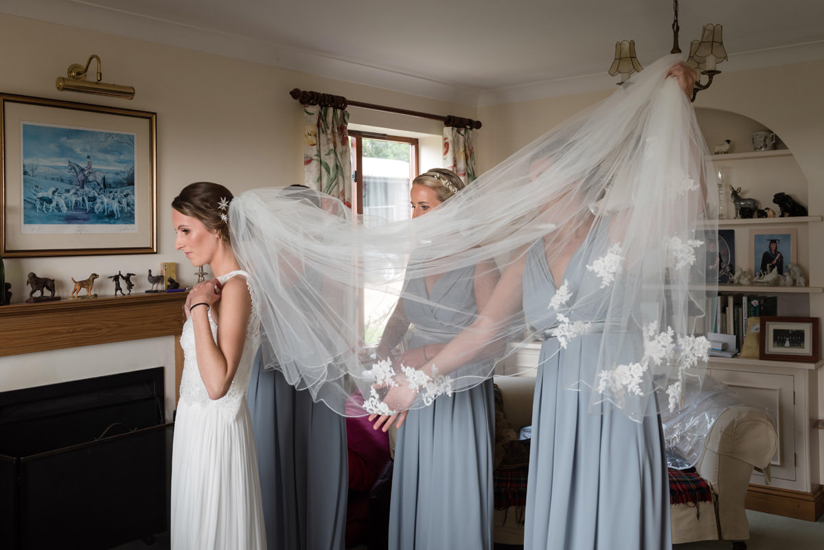 Bridesmaids holding up the Bride's veil while they do up her dress