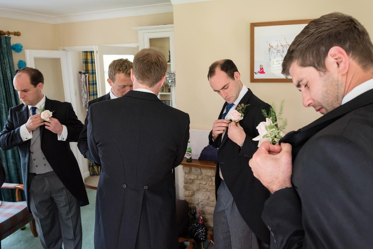 Groomsmen pinning button-holes in Maidwell, Northampton