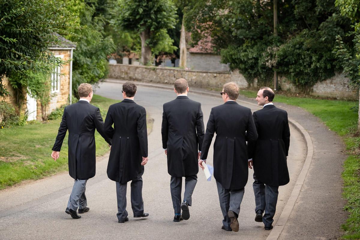 Groomsmen walking to Maidwell church in Northampton