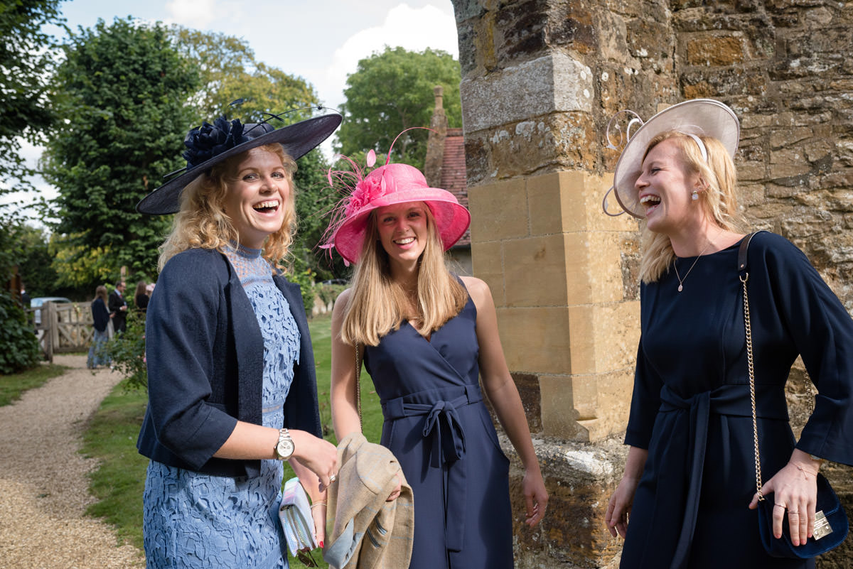Wedding guests laughing as they spotted the photographer at Maidwell church in Northampton