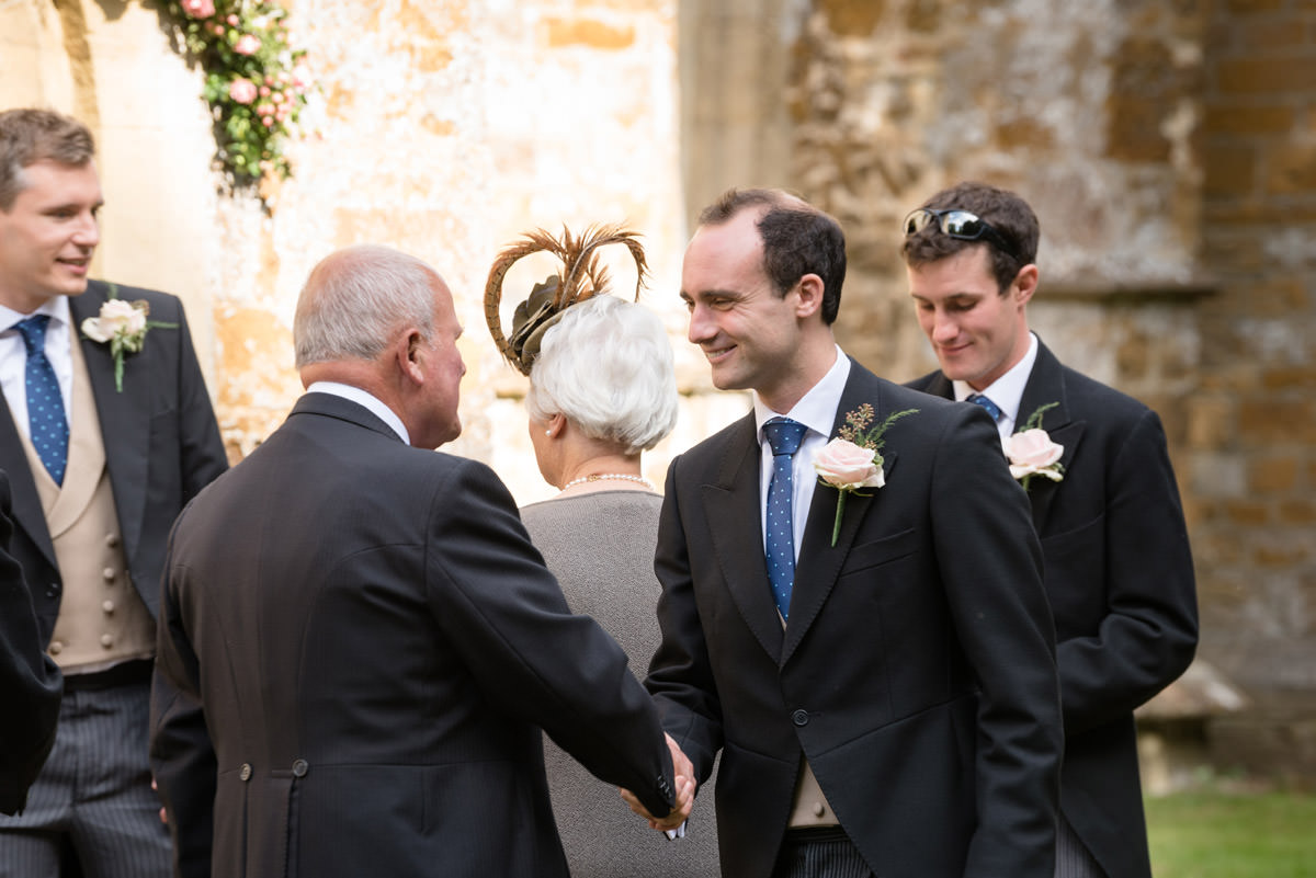 Groom greeting a wedding guest at Maidwell church in Northampton